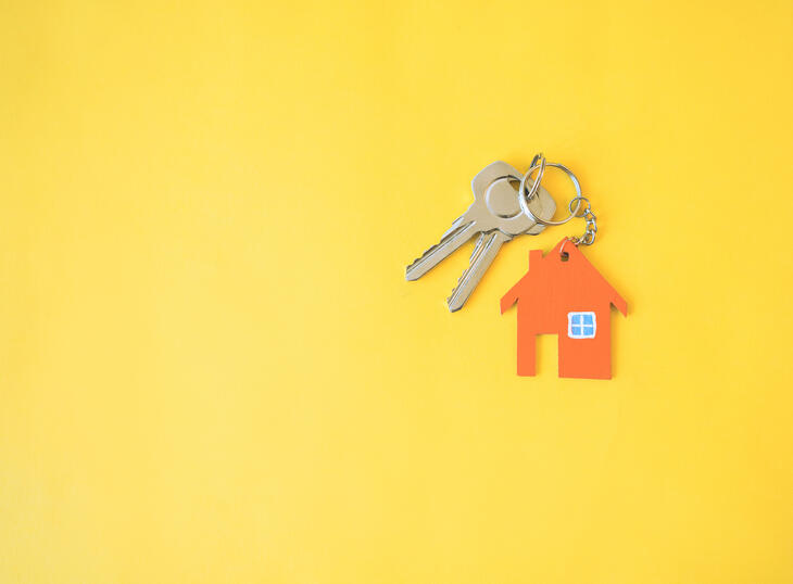 Key with house-keychain on yellow background